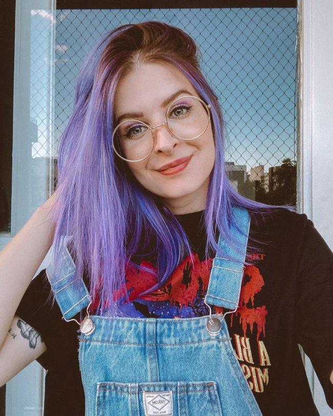 Jovem com uma das mãos na cabeça, com o cabelo roxo, usando óculos, com camiseta preta e jardineira jeans.