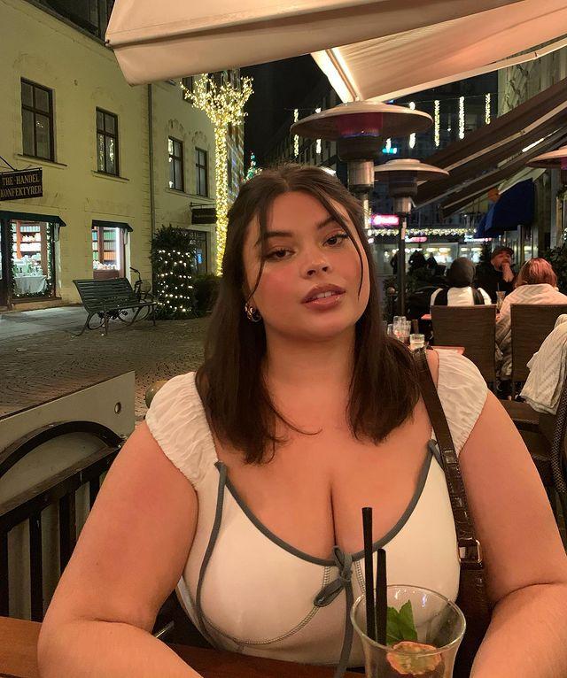 Jovem sentada em um restaurante com mesa na calçada, usando blusa com decote, e cabelo semi presto, posando para câmera.