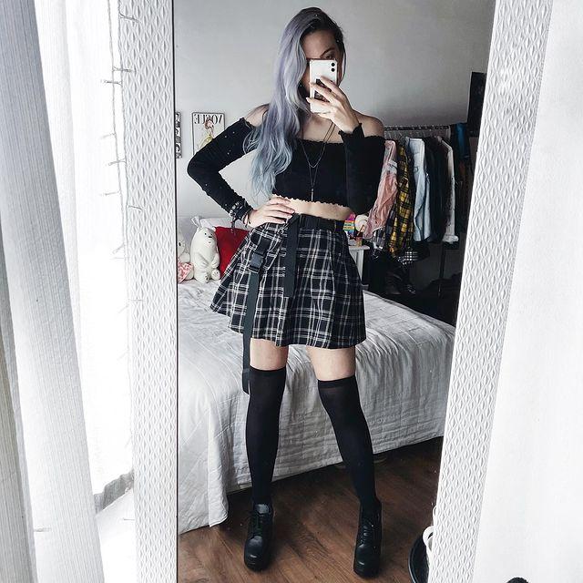 Jovem com blusa cropped preta, saia xadrez preta e meia 3/4 da mesma cor. Com a mão na cintura posando frente ao espelho.