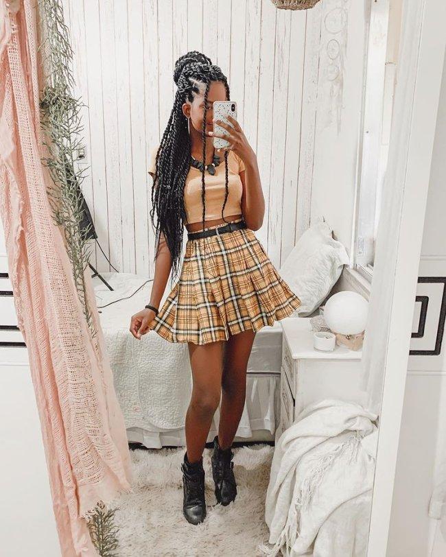 Jovem posando frente a espelho com cropped, saia xadrez com cinto fino, maxi colar preto, e bota preta.