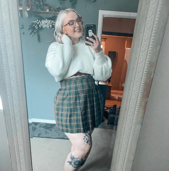 Jovem de óculos, posando frente ao espelho com um celular com capinha de fantasma, usando uma blusa branca com saia xadrez verde.