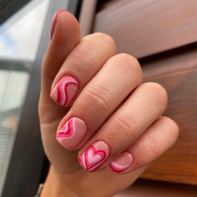 Na imagem temos uma mão exibindo as unhas com desenhos de coração vermelho e vazado por dentro e alguns espirais.