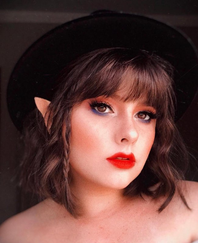 Jovem com chapéu preto, batom vermelho, delineado preto, olhando para câmera com expressão séria.