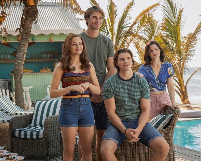 Elle, Noah, Lee e Rachel usando roupas de verão e sorrindo levemente para foto