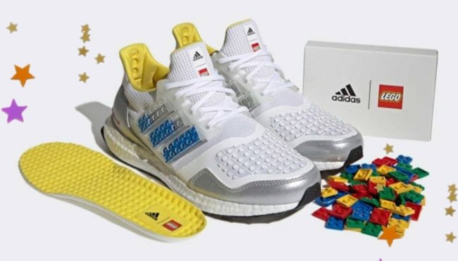 Foto com fundo branco, mostrando um par de tênis da adidas, com peças de lego espalhadas na frente do tênis, os tênis no lugar das listras pretas tradicionais da adidas, tem peça de lego azul.
