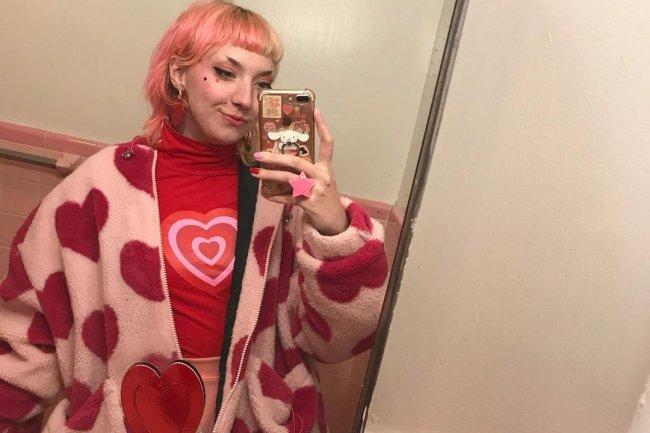 Jovem posa para foto frente a espelho, podemos ver o celular cobrindo parcialmente seu rosto que sorri para a foto, a jovem usa uma camisa vermelha com estampa de coração e um casaco rosa com vários corações vermelhos.
