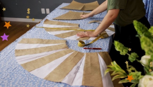 Mesa com vários moldes de roupas, podemos ver mãos trabalhando nos moldes, fita métrica, canetas e lápis espalhados pela mesa.
