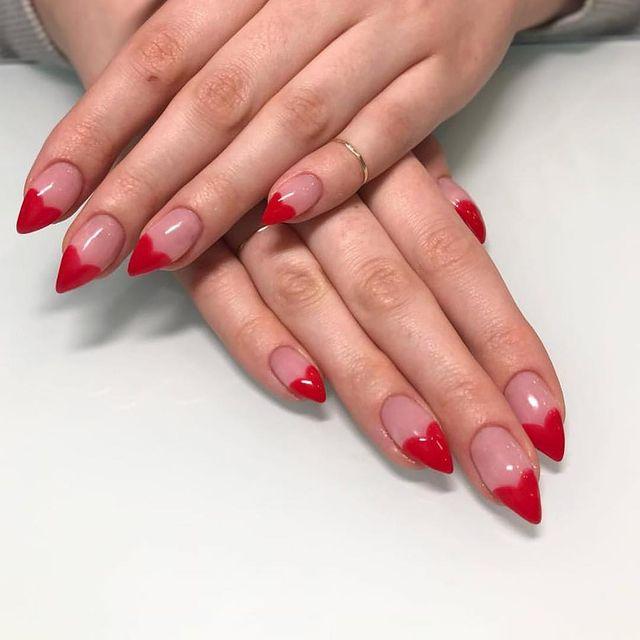 Na imagem temos uma mão exibindo as unhas com a pontinha pintada em formato de coração vermelho.