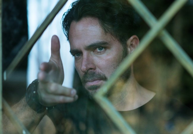 Álex Guzman apontando os dedos como se fosse uma arma através de uma janela