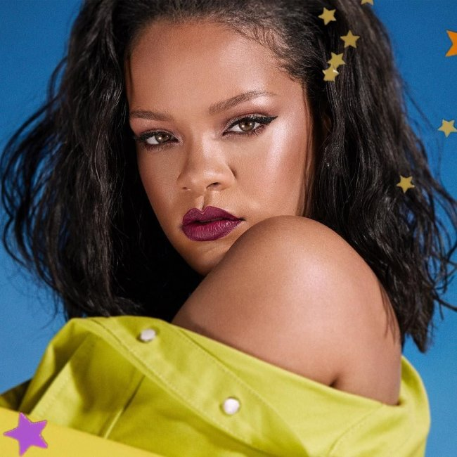Cantora Rihanna posando para foto com delineado gatinho, batom vermelho fechado, com expressão séria, de lado, com a camisa verde caída em seu ombro.
