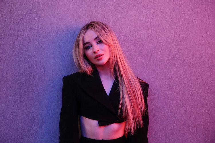 Cantora Sabrina Carpenter encostada na parede usando blusa preta com manga comprida estilo cropped, sua expressão é séria e ela está com a cabeça levemente inclinada para o lado esquerdo. A parede branca está iluminada por uma luz roxa.