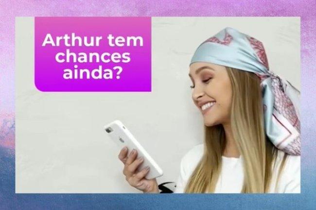 Carla Diaz usa lenço na cabeça, camiseta branca, sorri e segura celular. Na imagem está escrito