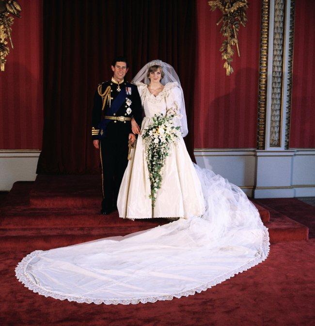 Princesa Diana e príncipe Charles em seu casamento em 1981, os dois aparecem sorridentes posando para foto. Charles usa seu traje de principe e Diana está com seu icônico vestido branco de noiva exibindo sua enorme cauda.