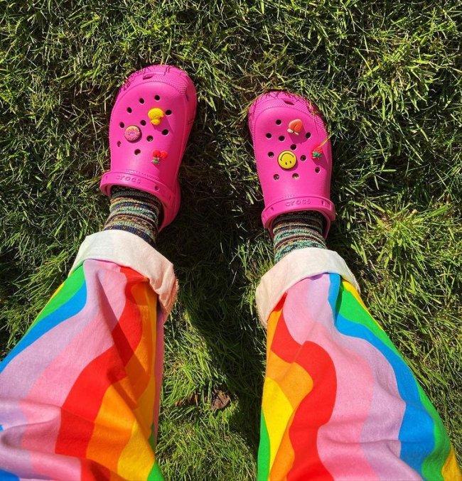 Foto mostrando somente parte da calça colorida com crocs rosa com pingente colorido de smile e frutas