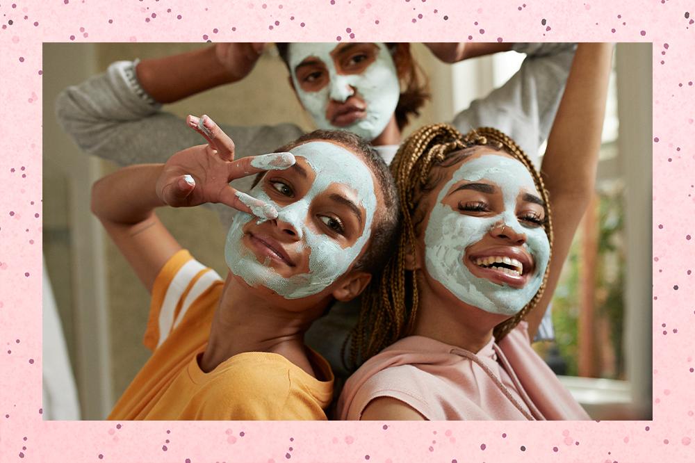 Três meninas usando máscaras faciais de argila. Duas estão na frente, uma olhando para o lado e fazendo o símbolo de paz e amor com os dedos, e a outra sorrindo com o olhar para baixo. Uma está ao fundo fazendo bico com a boca e os dois braços dobrados em direção à cabeça.