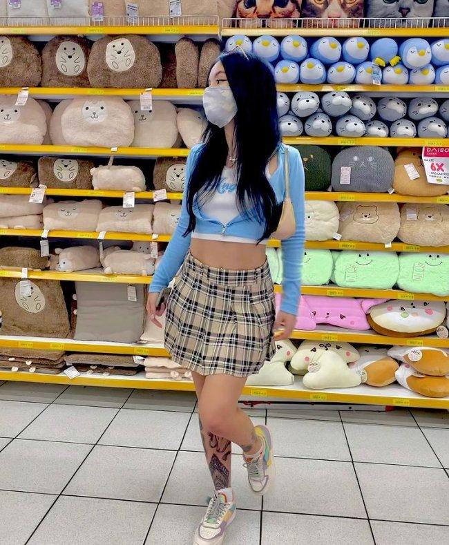 Jovem posando em frente uma prateleira cheia de ursinhos coloridos, usando uma blusa branca cropped, um moletom azul cropped, saia xadrez e tênis colorido.