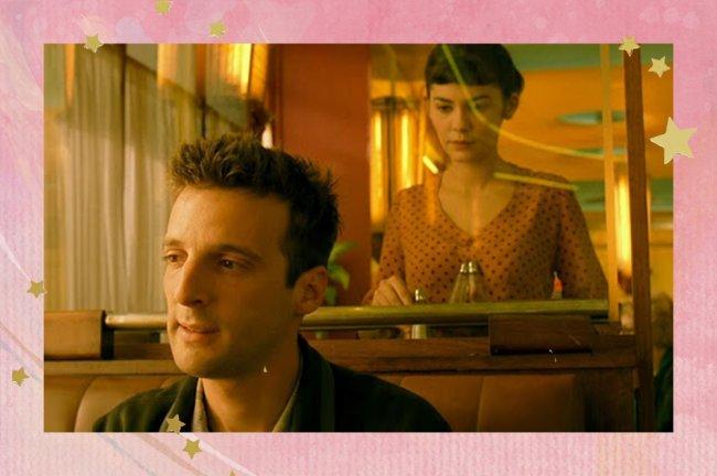 Amélie olha para Nino através e um vidro do café em que trabalha. Ela está em pé e ele sentado em uma das mesas