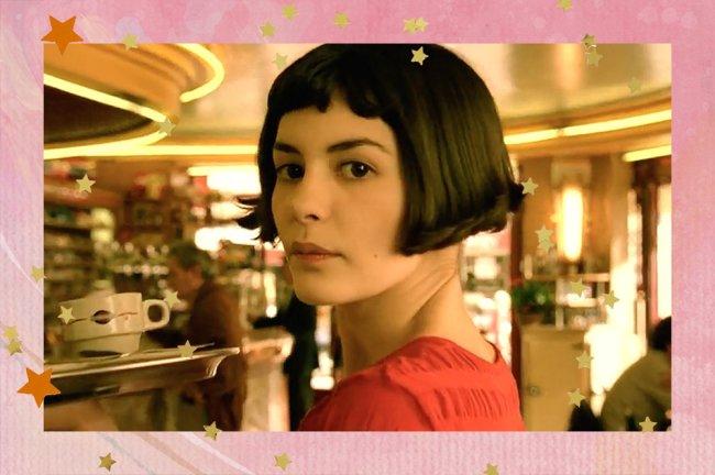 Amélie Poulain, interpretada por Audreu Tautou, aparece de cabelos curtos e camiseta vermelha. A personagem está no café em que trabalha e olha para o lado