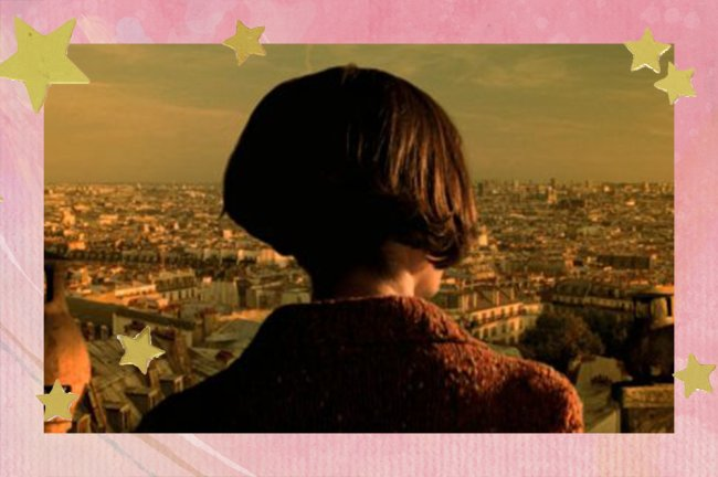 Amélie aparece de costas, usando um casaco marrom, e observando a vista de Paris da Basílica de Sacré Cœur