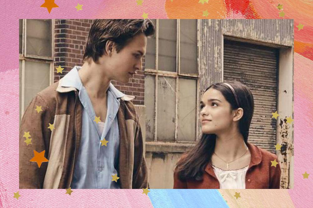 Ansel Elgort e Rachel Zegler em cena do filme Amor, Sublime Amor; os atores estão olhando um para o outro, ele usa uma camisa azul clara com casaco marrom e ela uma blusa branca com casaco vermelho