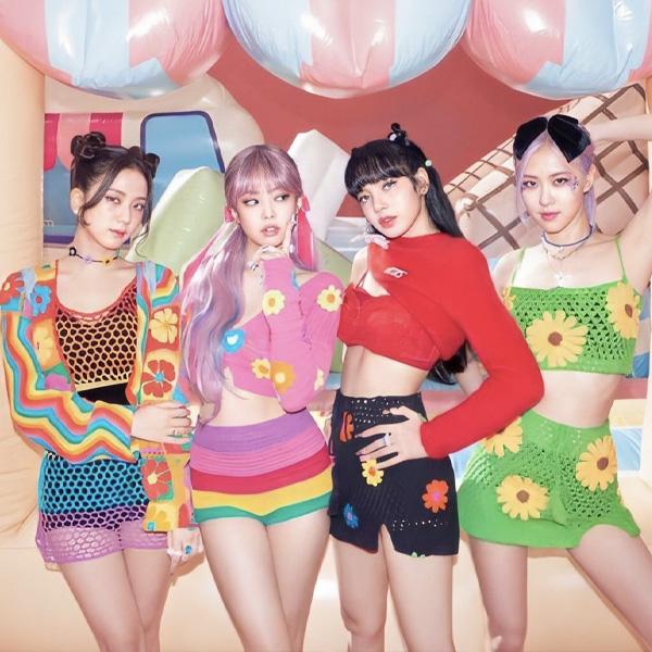 Grupo Blackpink no clipe de Ice Cream parceria com Selena Gomez, as meninas do grupo usam roupas coloridas com listras divertidas, flores, e posam em frente ao cenário que parece uma sorveteria.