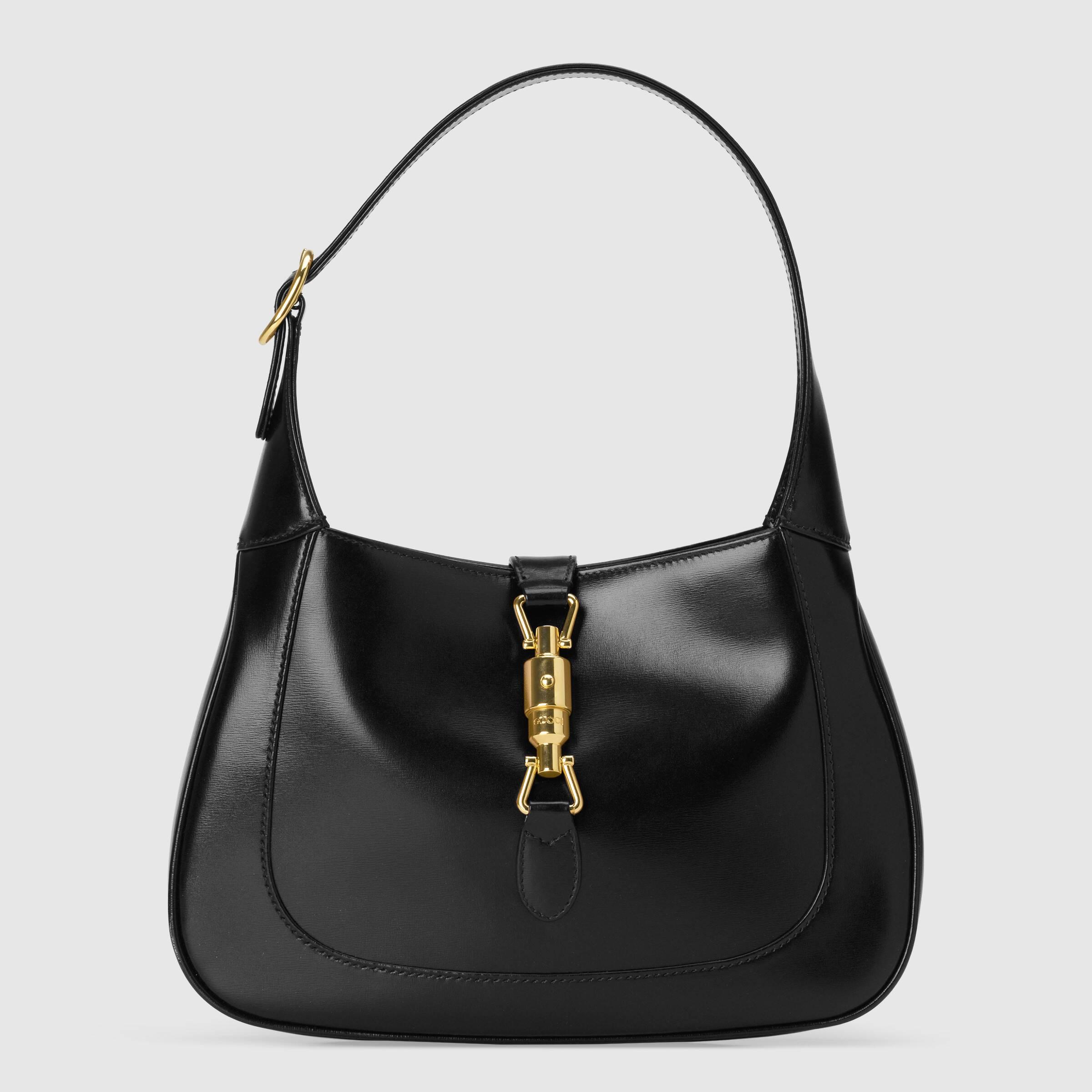 Foto da bolsa modelo Jackie 1961, da Gucci, que foi usada por Harry Styles em campanha da marca. A bolsa é preta de couro, tem alça curta, formato arredondado e um fecho dourado na frente. O fundo da foto é liso com tom acizentado.