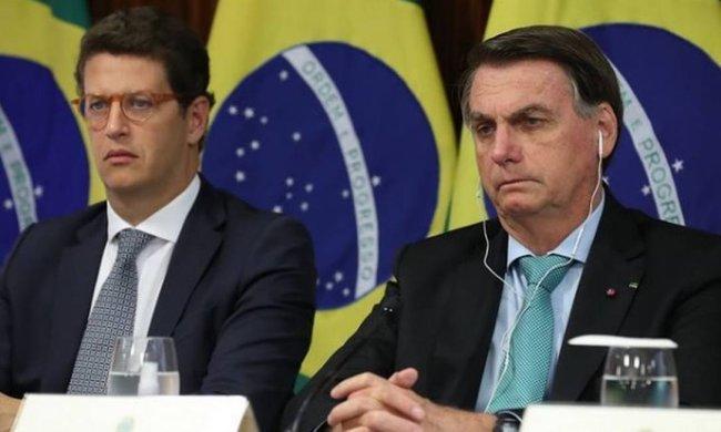 Jair Bolsonaro sentado ao lado de Ricardo Salles durante Cúpula do Meio Ambiente. Ao fundo, aparece a bandeira do Brasil