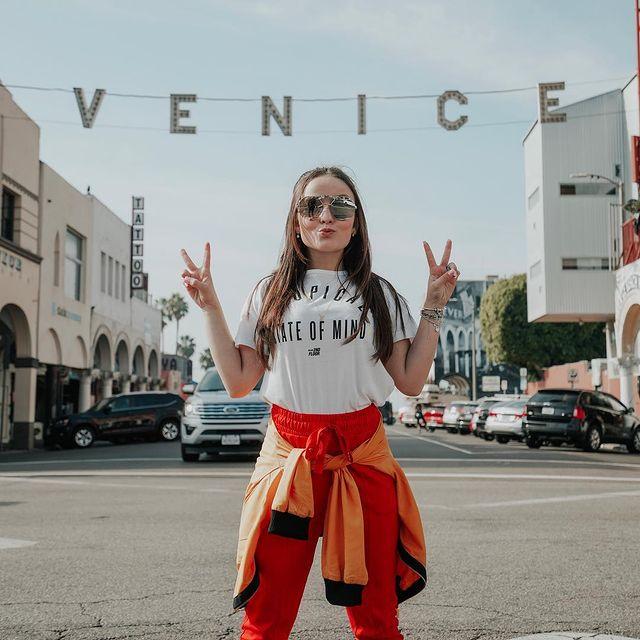Atriz Larissa Manoela posa em rua de Venice (LA) com calça vermelha, camiseta branca e blusa laranja amarrada na cintura