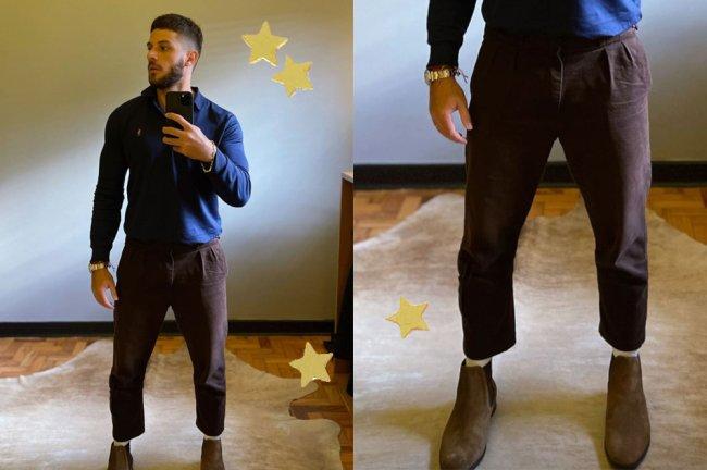 Chay Suede tirando uma foto no espelho; ele usa uma calça cigarrete marrom e uma camisa social azul de manga longa