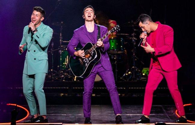 Jonas Brothers se apresentando em Detroid com a turnê Happiness Begins; o Nick veste um conjunto azul turquesa, o Kevin um roxo e o Joe um pink