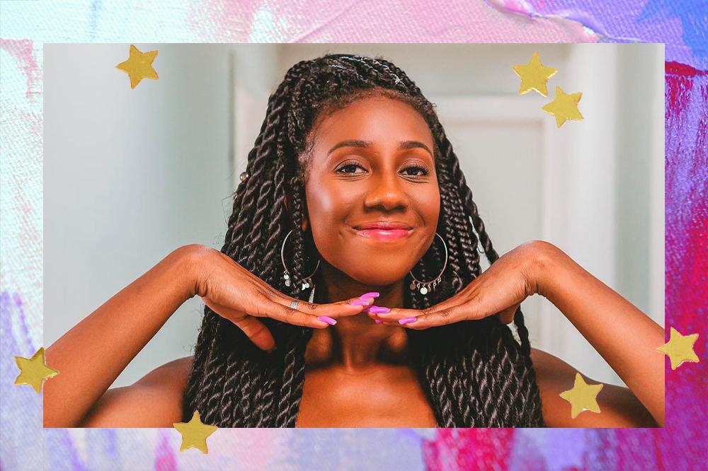 Montagem com foto da Camilla de Lucas dando um leve sorriso, sem mostrar os dentes, com as mãos embaixo do queixo. Ela está de tranças no cabelo e uma maxiargola nas orelhas. O fundo da montagem é rosa e lilás e tem algumas estrelinhas douradas nos cantos da foto.