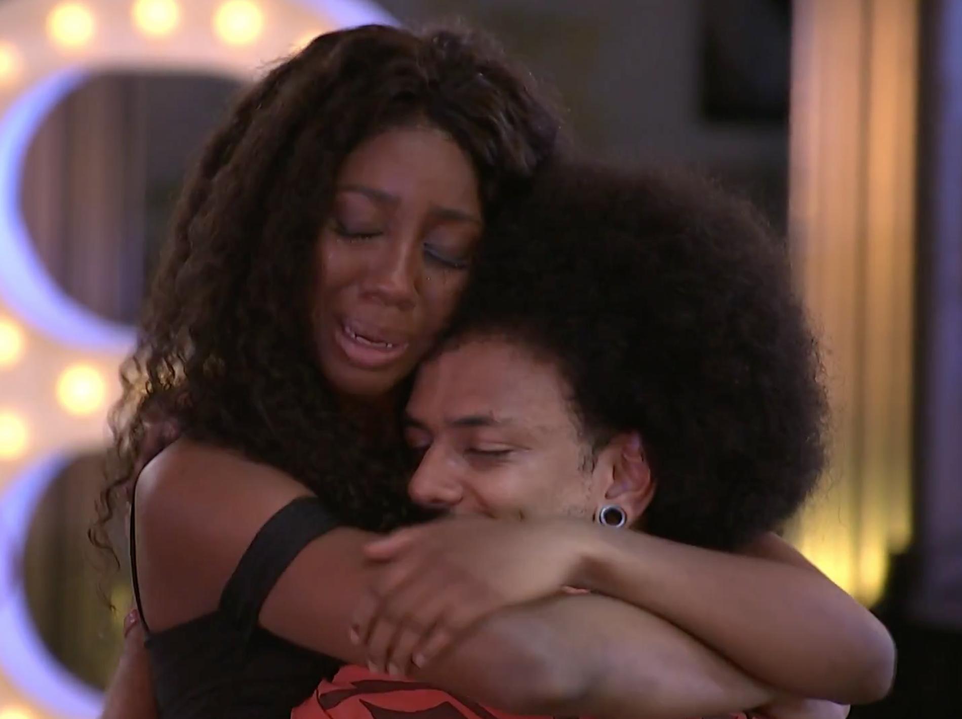 Camilla de Lucas e João Luiz abraçados no BBB21. Ambos estão de olhos fechados. Camilla chora