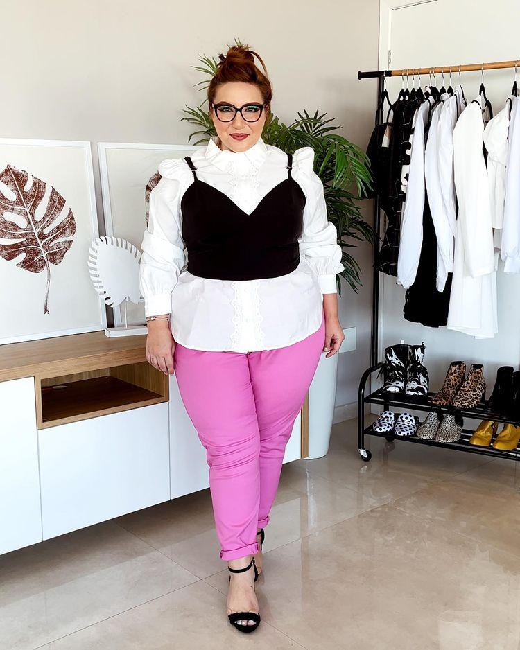 Garota usando camisa branca com corset preto por cima. Ela está com uma calça rosa e uma sandália preta de duas tiras, além de óculos de grau pretos. Ela está em pé com expressão séria, olhando para frente.