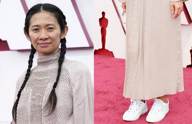 A diretora Chloé Zhao veste um vestido de manga longa nude e um tênis branco no tapete vermelho do Oscar