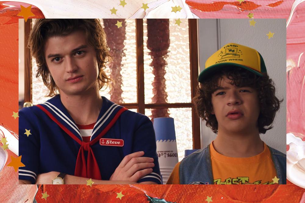 Steve e Dustin, de Stranger Things, um ao lado do outro. Steve com os braços cruzados e Dustin com expressão confusa