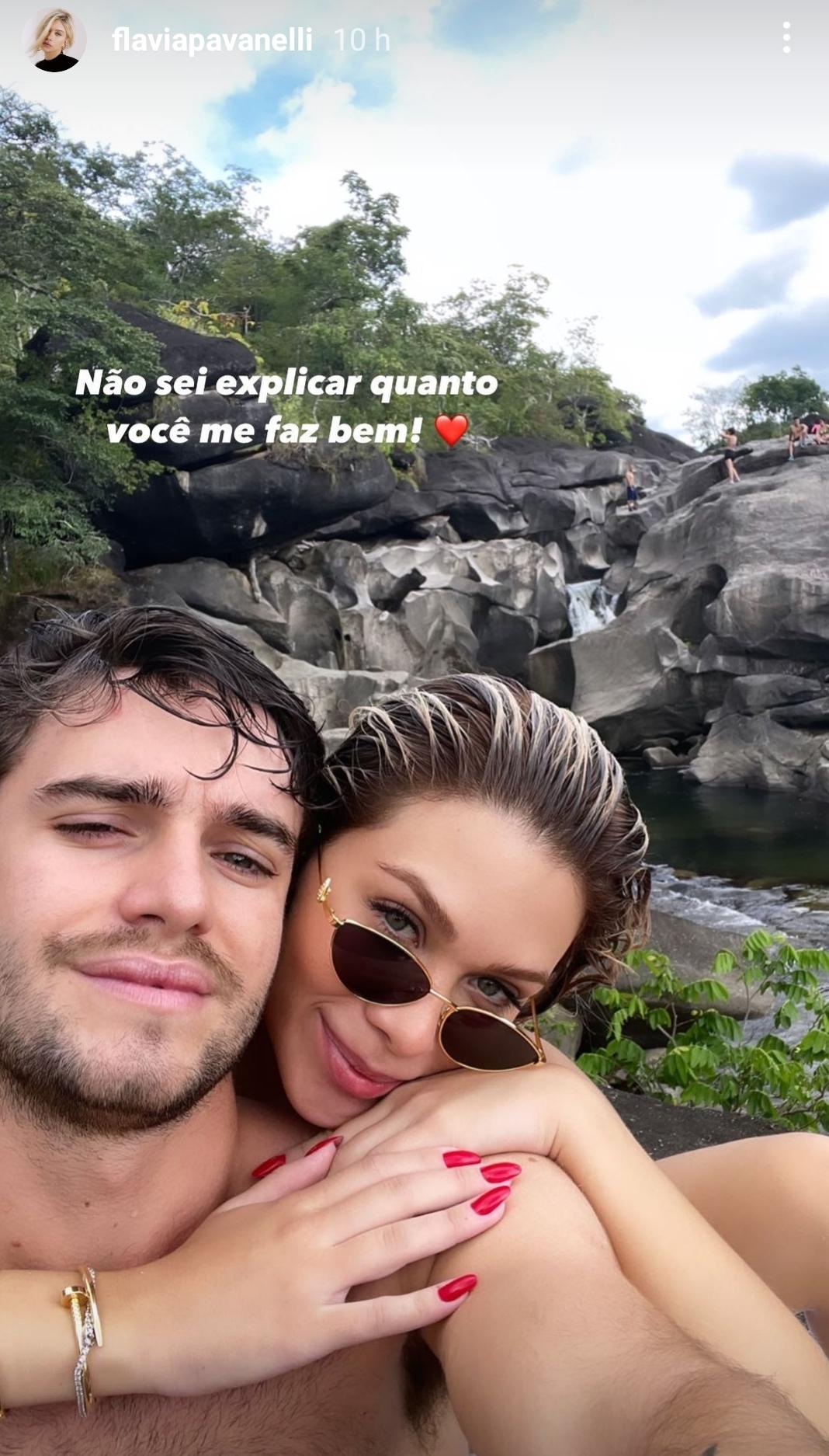 Flavia Pavanelli abraçando seu novo affair, Pepe Cruz. Ela está por trás dele e usa um óculos de sol. A expressão facial dele é séria. Ao fundo deles, há um cenário de natureza.