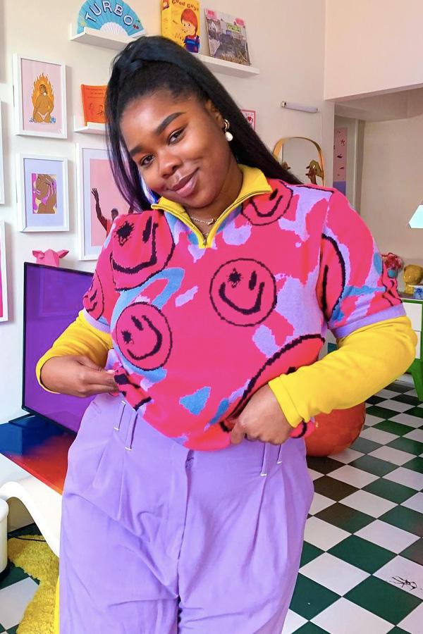 Jovem com as mãos no bolso, usando camisa com gola amarela e cor de rosa com smiles pretos, calça lilas e blusa amarela por baixo.