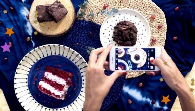 Mesa com toalha azul, com pratos, e bolos, sendo eles: red velvet, cupcake de chocolate e brownie. Também conseguimos ver duas mãos segurando um celular posicionado para fotografar a composição da mesa.