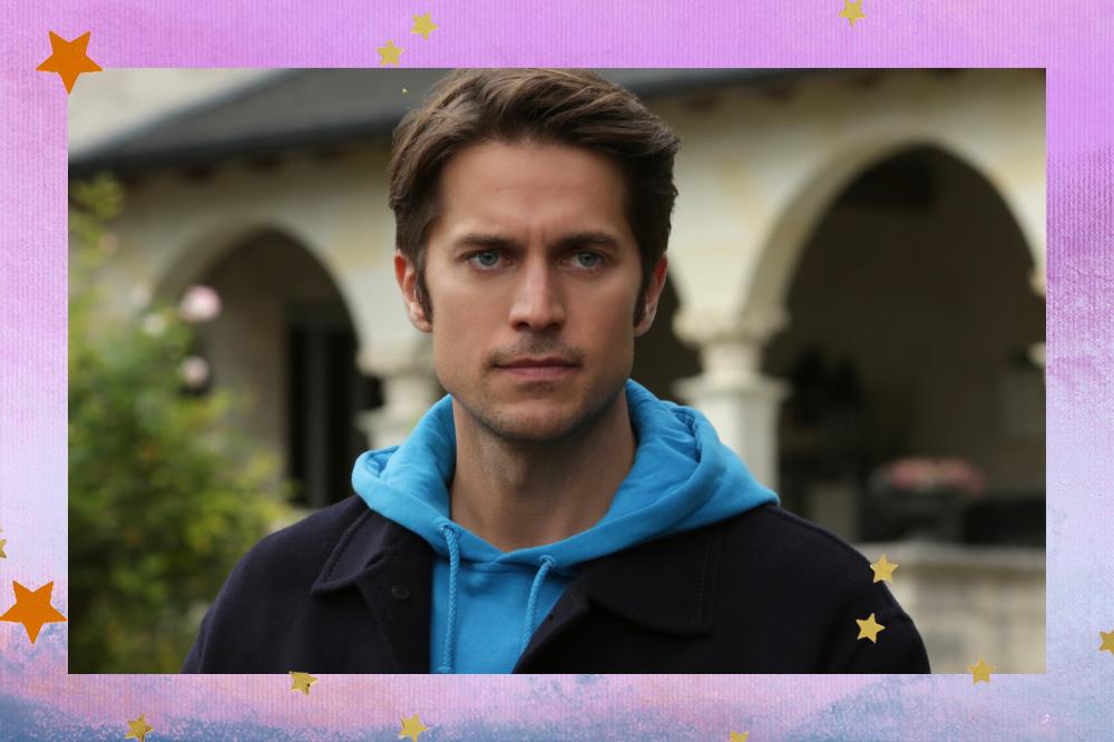 Gabriel em cena de Emily em Paris com casaco e moletom azul de capuz