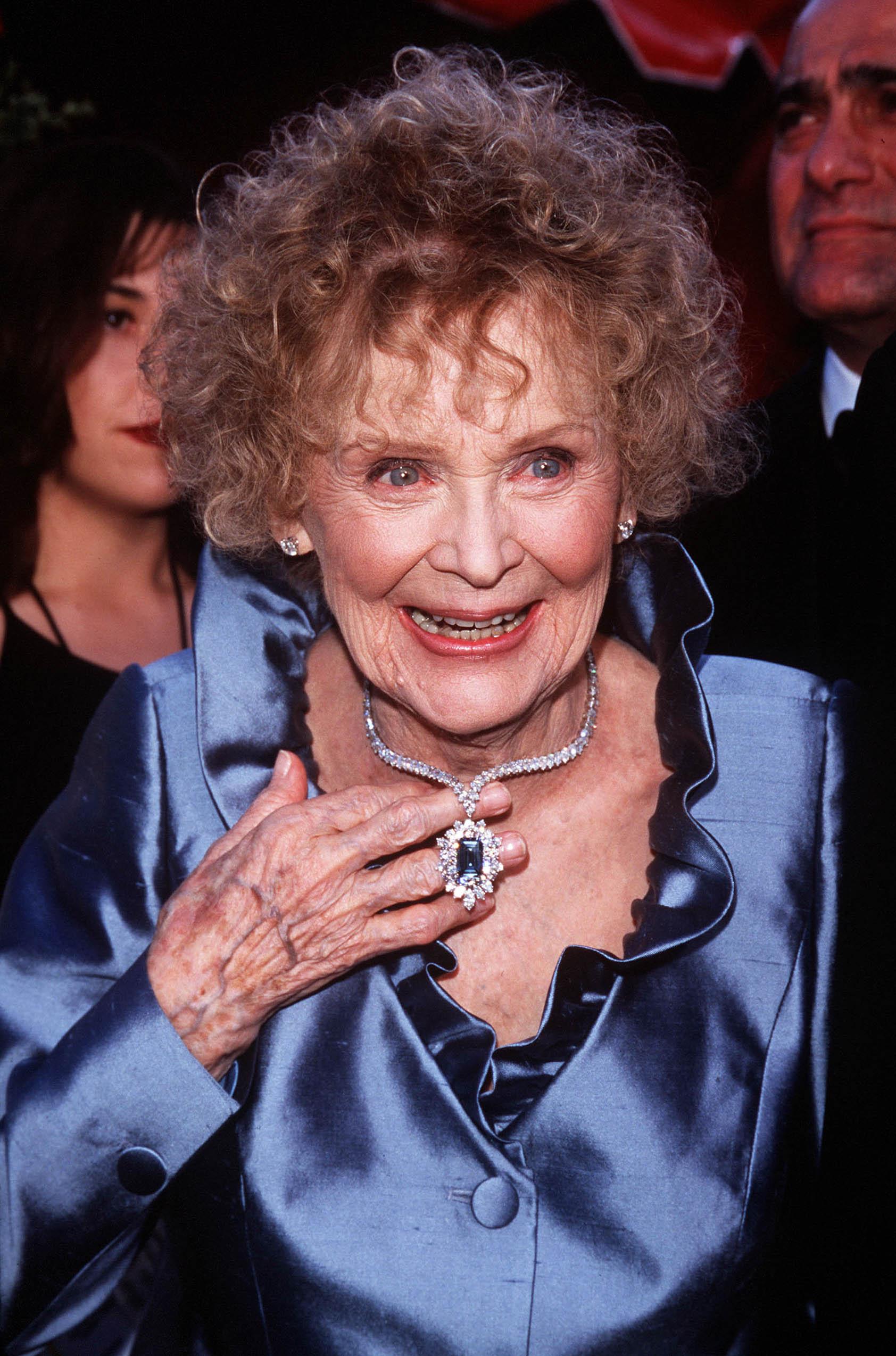 A atriz Gloria Stuart no Oscar de 1998. Ela está usando uma camisa azul de seda com babados na gola. Uma das suas mãos está segurando seu colar, que é todo de diamantes e tem um pingente com uma pedra azul no meio. Ela está sorrindo e olhando levemente para o lado direito.