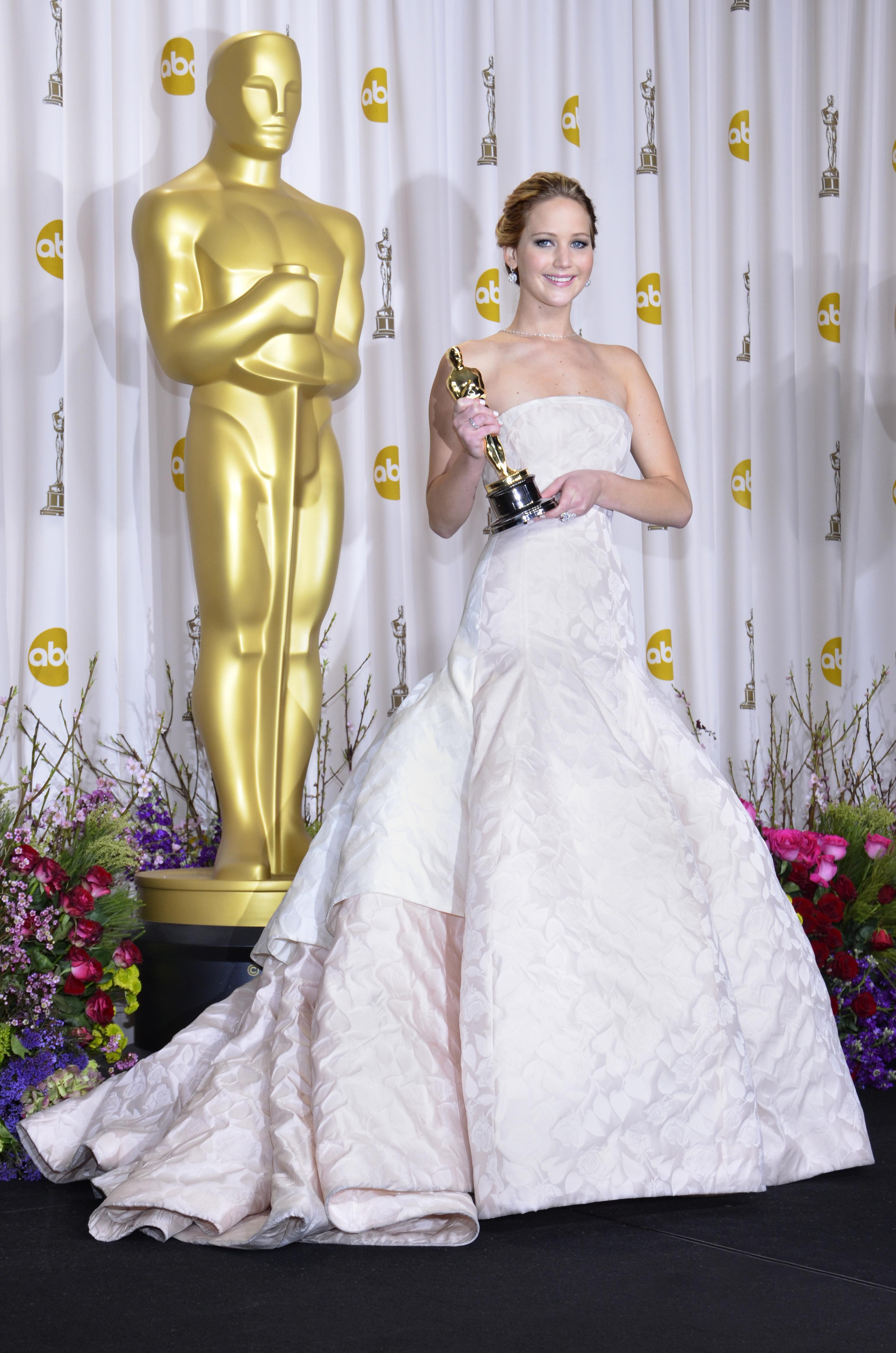 Jennifer Lawrence no tapete vermelho do Oscar 2013. Ela está usando um vestido longo, sem alça, na cor branca, com parte de cima justa e saia volumosa com uma estampa floral também branca e uma textura em alto-relevo. Ela está sorrindo e segurando uma estatueta do Oscar com as duas mãos.