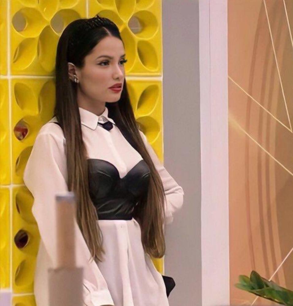 Juliette Freire no Big Brother Brasil 21 usando camisa branca, corset preto e tiara preta. Ela está encostada em uma parede amarela, com expressão facial séria, e a foto foi tirada de lado.