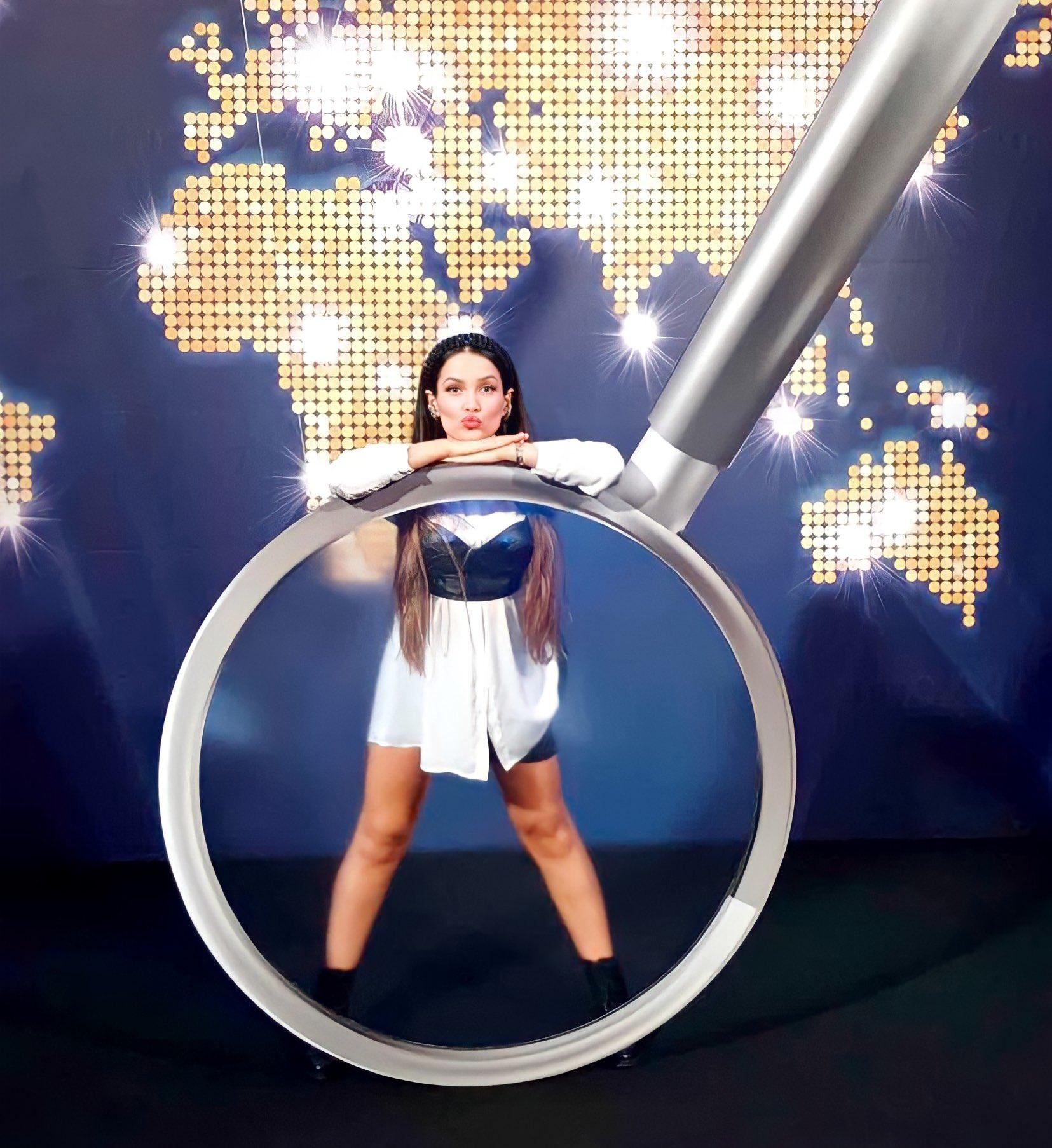 Juliette Freire em festa do Big Brother Brasil 21. Ela está usando camisa branca, corset preto, bermuda ciclista preta e coturno preto, além de tiara preta brilhante. Ela com os dois braços apoiados em uma luneta gigante, enquanto faz careta de bico com a boca.