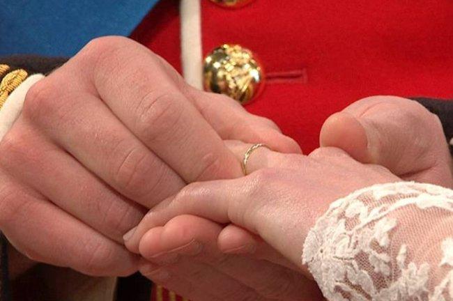 William colocando a aliança de casamento no dedo de Kate durante o Casamento Real. Ela é bem fininha e dourada