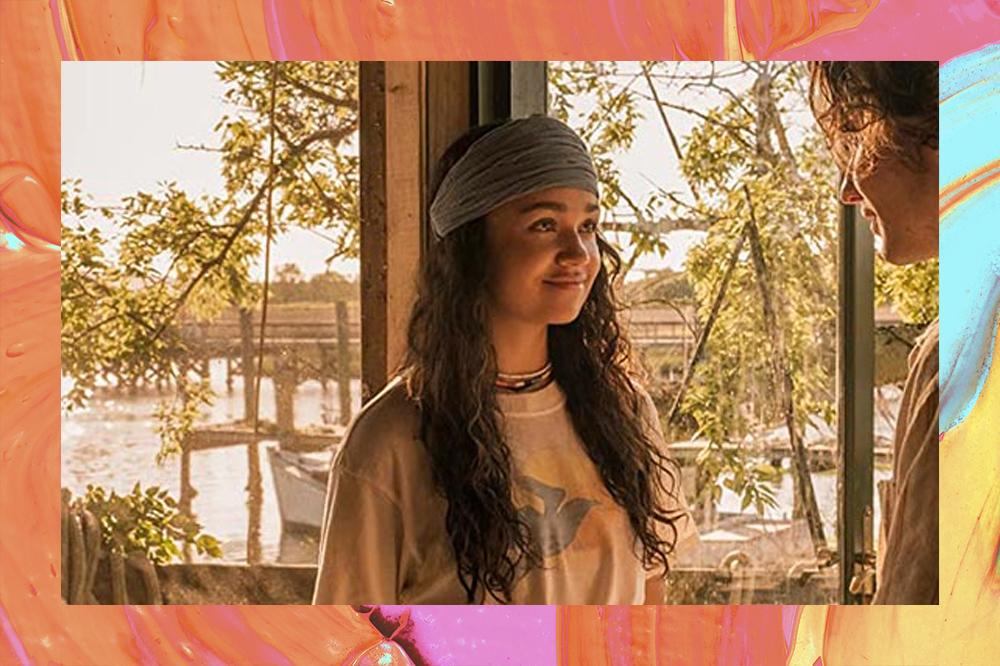 Kiara sorrindo em cena de Outer Banks com paisagem natural no fundo