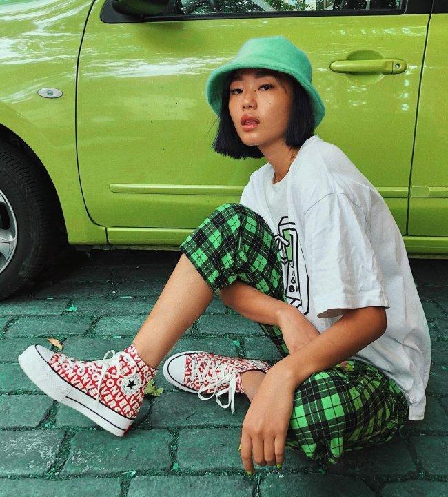 Jovem asiática sentada no chão com all star vermelho com letras brancas, calça xadrez verde e camisa branca larga em frente a carro verde.