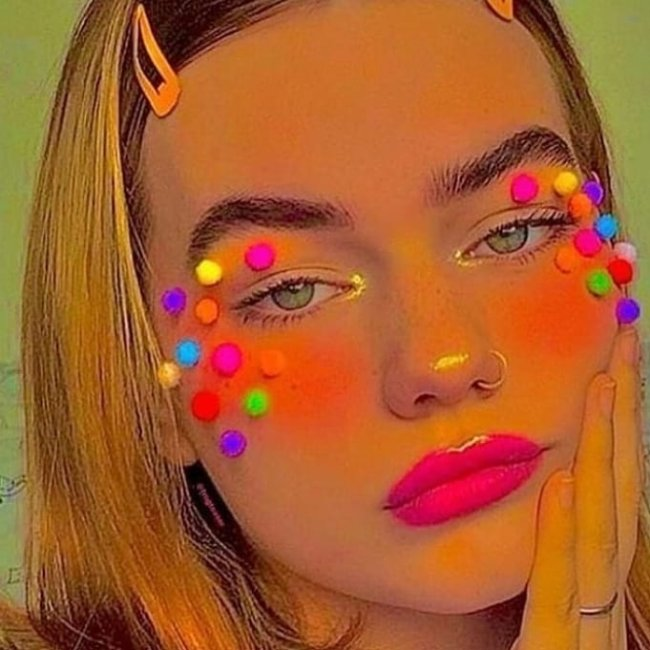 Jovem posando para foto com close em seu rosto, com maquiagem com o canto do olha iluminado e muito blush nas bochechas com bolinhas coloridas coladas ao redor dos olhos, batom rosa neon e uma das mãos apoiadas no rosto.