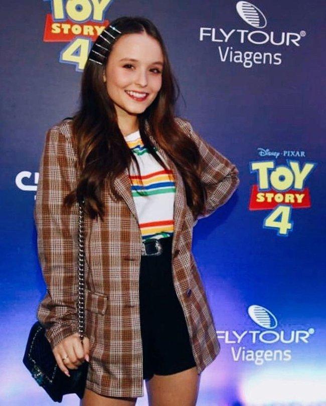 Larissa Manoela posa em pré-estreia do filme Toy Story 4, usando uma camiseta branca com listras, short jeans e blazer xadrez