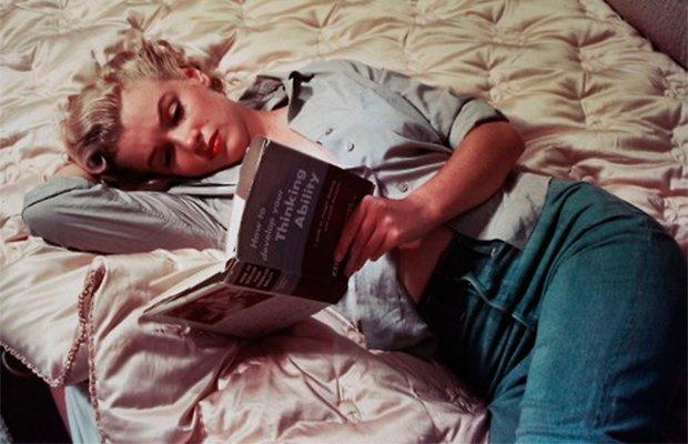 Marilyn Monroe aparece deitada e segurando um livro