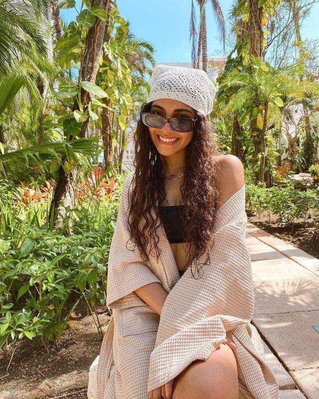 Nour, do Now United, posa com óculos escuros, cabelo solto, usando lenço branco com furinhos, em frente a vários coqueiros com top preto e blusa de lã bege.
